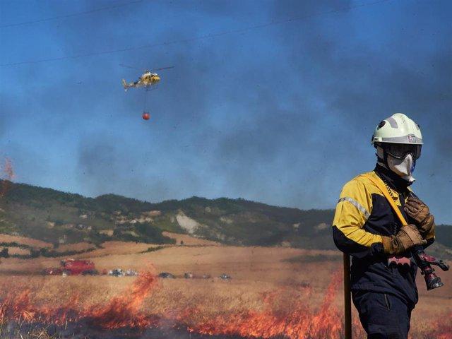 Un bombero y un helicóptero de la Brigada Helitransportada del Gobierno de Navarra realizan labores de extinción de un incendio forestal producido en una zona de campo de cereal, sin afectar a zonas urbanas, cerca de la localidad navarra de Sarriguren, a