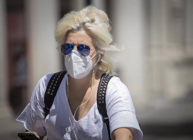 Una mujer con mascarilla y gafas de sol  durante el quinto día de la fase 2 en Sevilla (Andalucía, España), a 29 de mayo de 2020.