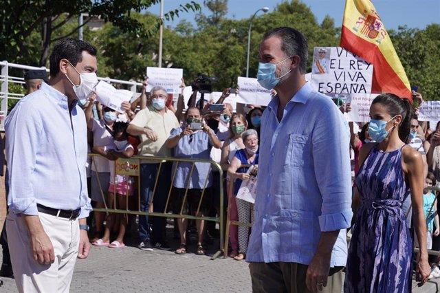 El presidente de la Junta de Andalucía, Juanma Moreno, saluda a los reyes Felipe VI y doña Letizia en Sevilla.