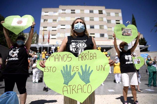Una trabajadora de limpieza del Hospital Gregorio Marañón sujeta un corazón verde -que reivindica la importancia de los servicios públicos en Sanidad- en el que reza 'Manos arriba esto es un atraco' a las puertas del hospital.