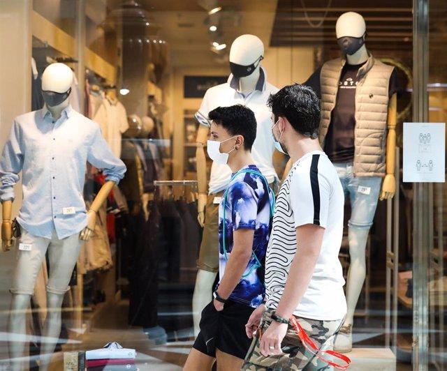 Dos jóvenes pasan junto a una tienda de ropa del Centro Plaza Norte 2, La Cúpula de Madrid, durante el segundo día de la Fase 2 de desescalada, y un día después de reanudar su actividad puesto que se permite la reapertura de centros comerciales mayores de