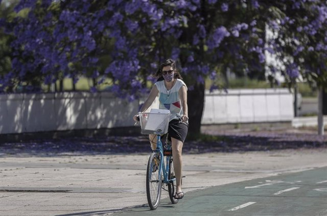Una mujer con mascarilla y ropa de verano circula en bicicleta por el Puente del Alamillo. En Sevilla (Andalucía, España), a 21 de mayo de 2020.