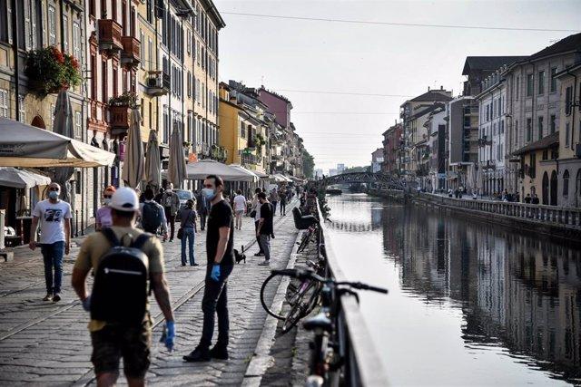 Personas con mascarilla paseando por Milán
