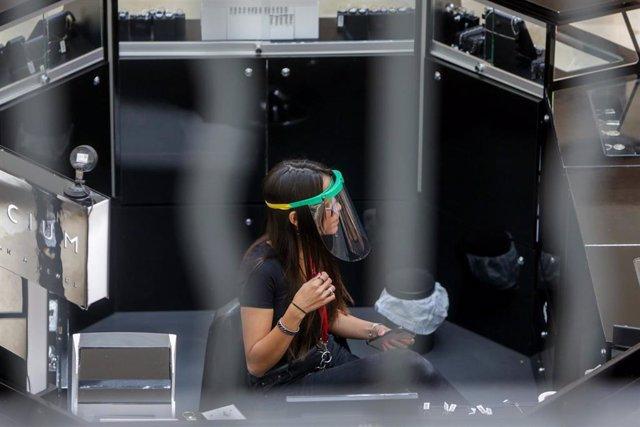 Una mujer protegida con una pantalla protectora trabaja durante la pandemia de coronavirus (Archivo)