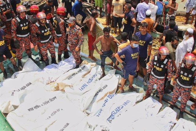 Miembros de los equipos de rescate marítimos junto a algunos de los cuerpos recuperados tras el hundimiento de un ferri en el río Buriganga, cerca de Daca, la capital de bangladesh, al chocar contra otra embarcación de mayor tamaño.