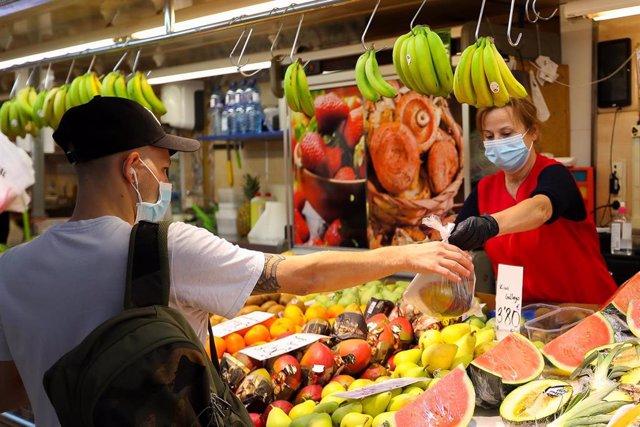Una trabajadora de una frutería del Mercado Central de Valencia atiende a un cliente