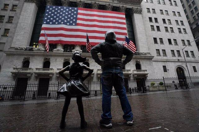 Un hombre junto a la estatua de la Niña sin miedo ante el edificio de la Bolsa en Nueva York