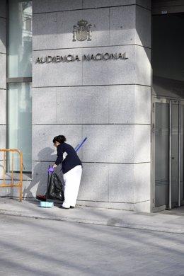 Una trabajadora de la lipieza barre la puerta pricipal de la sede de la Audiencia Nacional de Madrid.