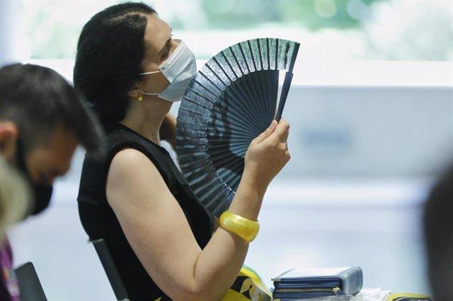 Una mujer con mascarilla se abanica en Madrid (España), a 29 de junio de 2020. El calor pone desde este lunes en aviso a una quincena de provincias de Andalucía, Castilla y León, Castilla-La Mancha, Extremadura y Madrid, por temperaturas máximas que van d