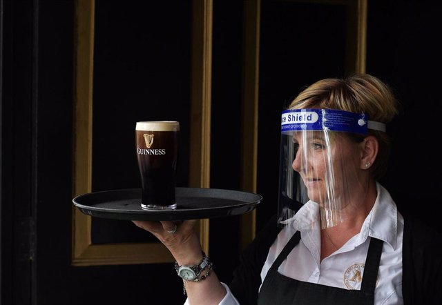 Camarera con protección frente al coronavirus con una bandeja con una pinta de cerveza negra en un pub de Dublín