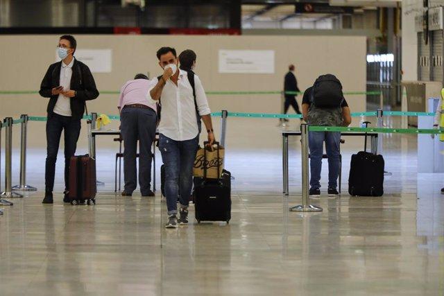 Pasajeros procedentes de Londres rellenan un formulario a su llegada como medida de seguridad para controlar los casos sospechosos de coronavirus