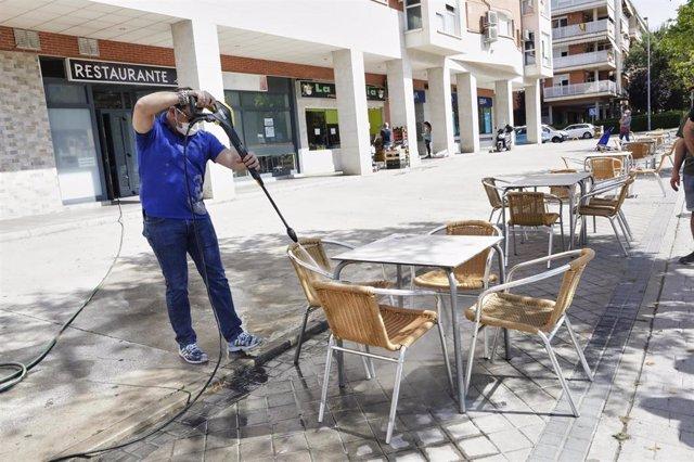 Un trabajador desinfecta la terraza de un restaurante antes de reabrir sus puertas en la desescalada ante la crisis sanitaria del Covid-19. En Valdemoro, Madrid, (España), a 23 de mayo de 2020.