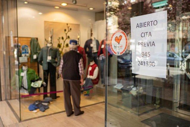 Un hombre observa el escaparate de un establecimiento abierto durante el tercer día desde que se decretó el estado de alarma , en Vitoria