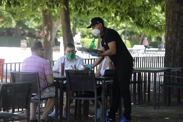 Un camarero protegido con mascarilla atiende a una mesa