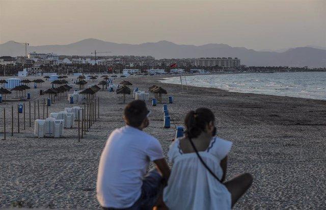 Dos jóvenes sentados contemplan la playa de la Malvarrosa durante la noche de San Juan en Valencia