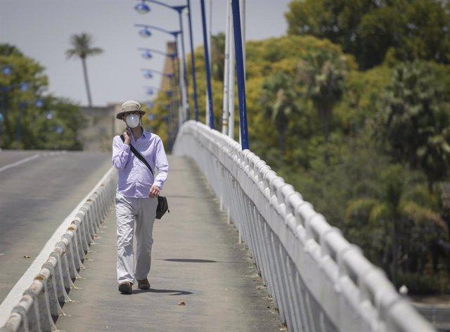 Un hombre con un gorro camina por la pasarela de la Cartuja durante la alerta naranja por altas temperaturas. En Sevilla (Andalucía, España), a 23 de junio de 2020.