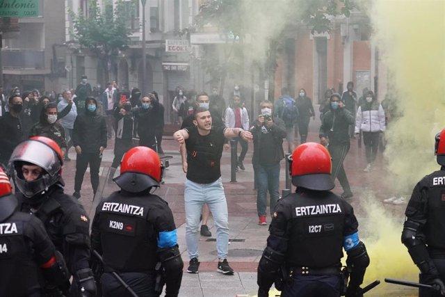Agentes de la Ertzaintza cargan contra un grupo de radicales que intentan boicotear un mitin del presidente de Vox, Santiago Abascal, en Sestao.