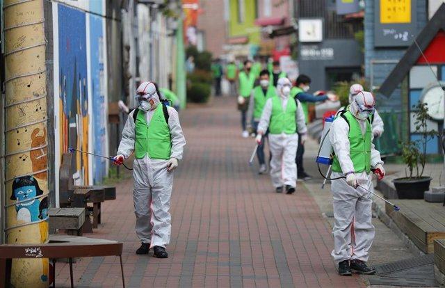 Un grupo de trabajadores desinfectan una calle de Corea del Sur.