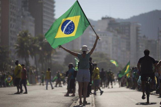 Una seguidora de Bolsonaro con una bandera de Brasil.