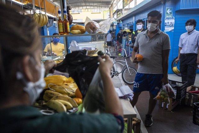 Un hombre hace cola para ser atendido en un puesto de frutas de un mercado de Lima, Perú, durante la pandemia de la COVID-19.