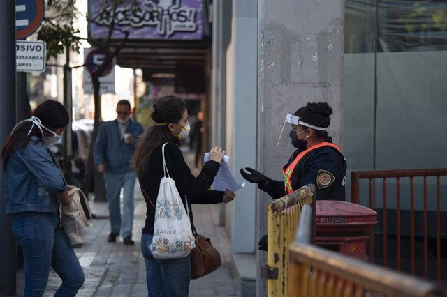 Una agente de la Policía comprueba el permiso de una ciudadana para circular por las calles de Córdoba en medio de las medidas de restricción de movimientos impuestas en Argentina para frenar la COVID-19.