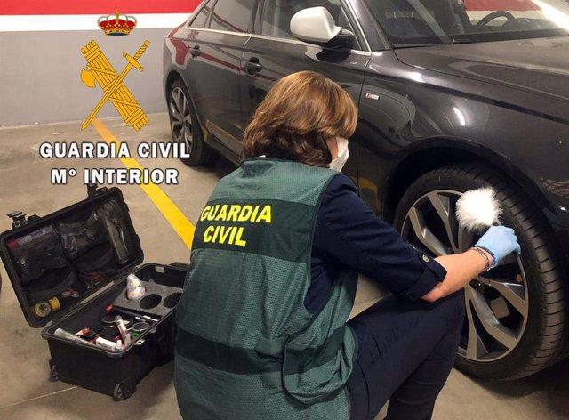Una agente de la Guardia Civil recoge vestigios de un vehículo