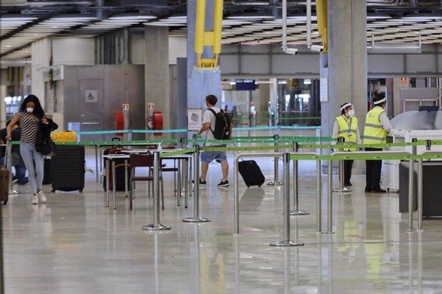 Pasajeros procedentes de Londres caminan entre los pasillos delimitados, antes de rellenar un formulario, a su llegada al Aeropuerto de Madrid-Barajas Adolfo Suárez, como medida de control de los casos sospechosos de coronavirus cuatro días después desde