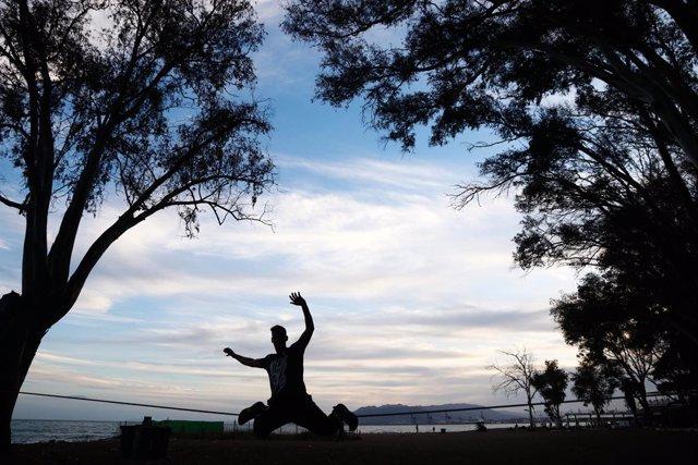 Un joven realiza prácticas del deporte Slackline.