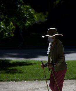 Una mujer camina con bastones en el Parque del Retiro en Madrid (España), a 29 de junio de 2020. El calor pone desde este lunes en aviso a una quincena de provincias de Andalucía, Castilla y León, Castilla-La Mancha, Extremadura y Madrid, por temperaturas