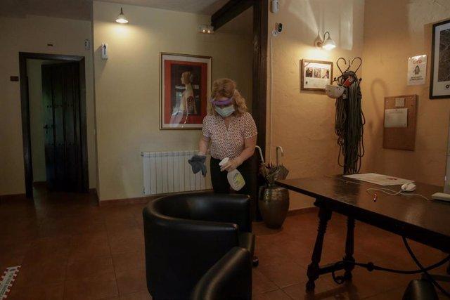 Una trabajadora protegida con mascarilla y mampara desinfecta dentro de las instalaciones de una casa rural