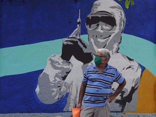 Un hombre con mascarilla ante un mural de un trabajador médico en Bombay