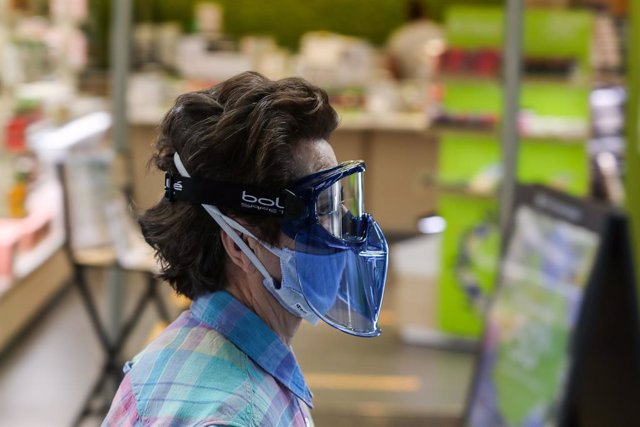 Una mujer protegida con mascarilla y gafas protectoras