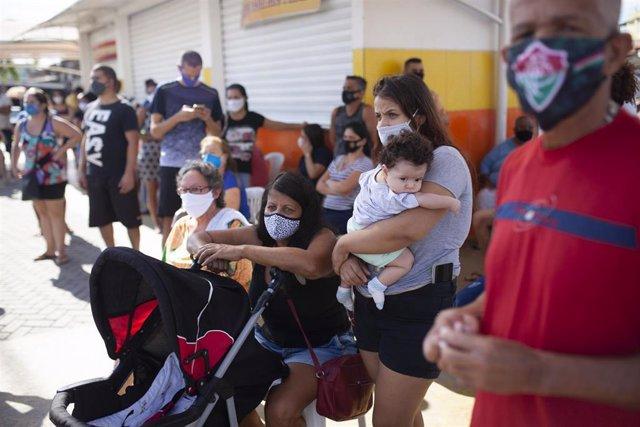 Personas hacen fila para hacerse la prueba del coronavirus durante un examen masivo en Río de Janeiro (Brasil) a 27 de junio de 2020