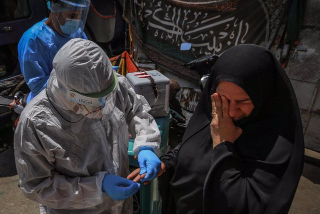 Un trabajador sanitario de Irak hace una prueba a una mujer para determinar si tiene coronavirus