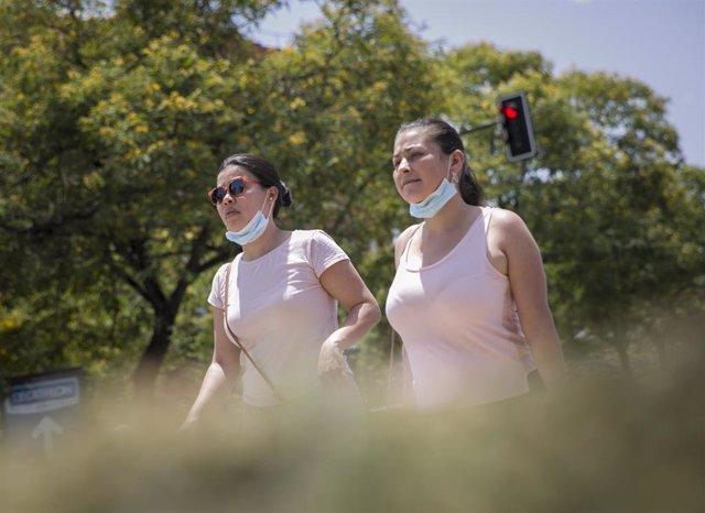 Dos mujeres caminan con la mascarilla bajada durante la alerta naranja por altas temperaturas. En Sevilla (Andalucía, España), a 23 de junio de 2020.