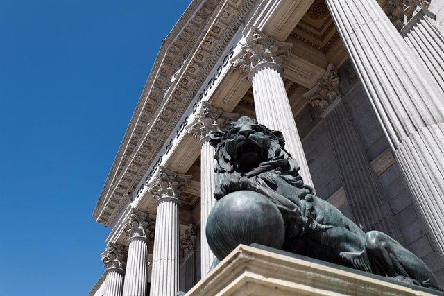 Uno de los emblemáticos leones que se encuentran delante de la fachada del Congreso de los Diputados en la Plaza de las Cortes de Madrid.