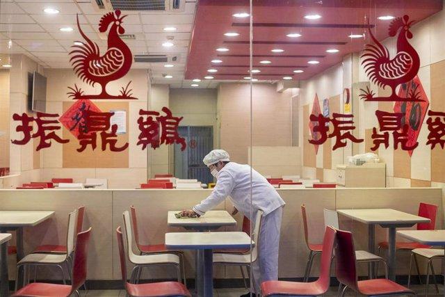 Un trabajador de un restaurante de Shanghái limpia una de las mesas del establecimiento durante la primera etapa de las medidas de confinamiento decretadas para frenar el avance de la COVID-19.