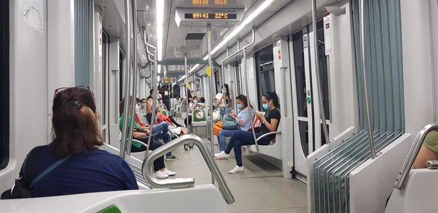 Usuarios del Metro de Sevilla, que refuerza su servicio un 21% durante la selectividad, con mascarillas