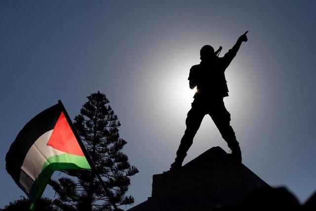 Un manifestante y una bandera palestina