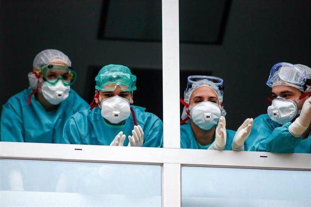 Varios sanitarios con protección EPI, mascarillas, gafas y guantes, aplauden en agradecimiento desde la ventana el homenaje a los Sanitarios celebrado en el Hospital Fundación Jiménez Díaz.