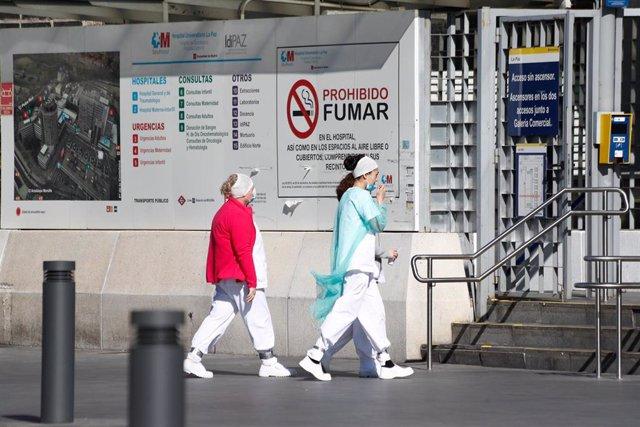 Dos sanitarias protegidas con mascarillas se dirigen a la entrada del Hospital La Paz.