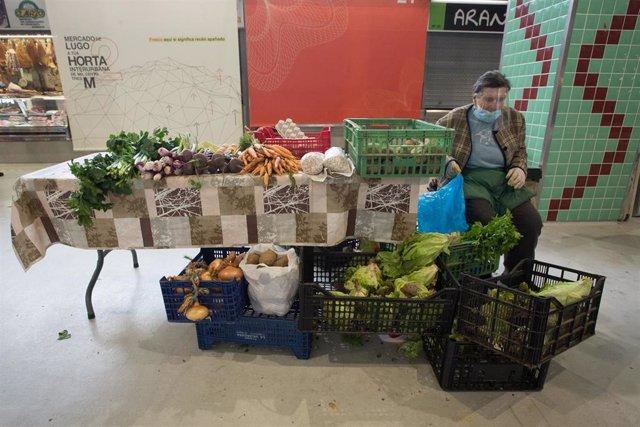 Una vendedora de verduras porta una pantalla facial en el Mercado Municipal de Lugo en la Fase 1  a 15 de mayo de 2020.