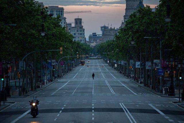 Una persona camina por el Paseo de Gràcia de Barcelona que amanece vacío un día marcado por la festividad de Sant Jordi, que a diferencia de otros años, este no se puede celebrar con normalidad debido a la crisis del Covid-19 y al confinamiento al que se