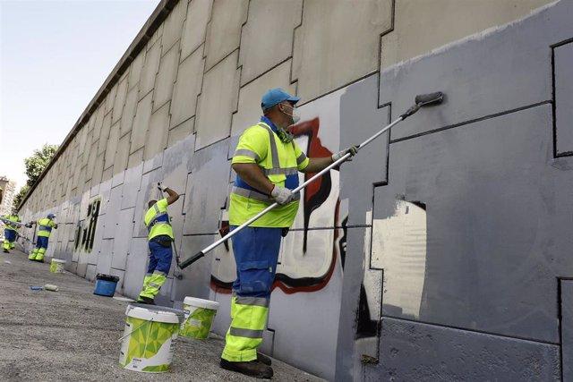Varios operarios limpian grafitis durante el comienzo de la campaña de limpieza de grafitis en Calle 30, trabajos que durarán dos meses y que supondrán la eliminación de 30.000 m2 de pinturas vandálicas. En Madrid (España), a 1 de junio de 2020.