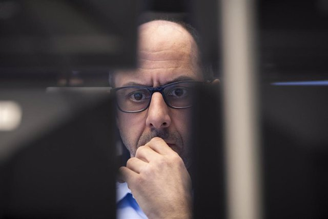 Un operador de mercados concentrado en las pantallas de información financiera