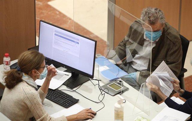 Una trabajadora de la Oficina de la Agencia Tributaria atiende a un hombre el día en el que la atención presencial en oficinas de la Agencia Tributaria para confeccionar la declaración de la Renta de 2019 se retoma