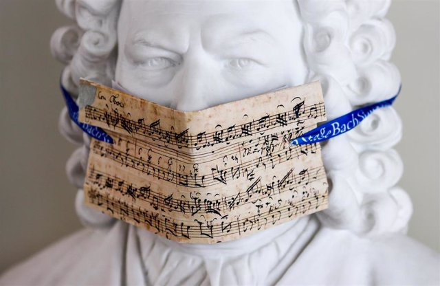 "12 May 2020, Leipzig: A bust of Bach with a face mask made of notes from the cantata ""My heart swims in blood"" is on display in the Bach Archive in front of the exhibition ""Bach and Beethoven. Photo: Jan Woitas/dpa-Zentralbild/dpa"