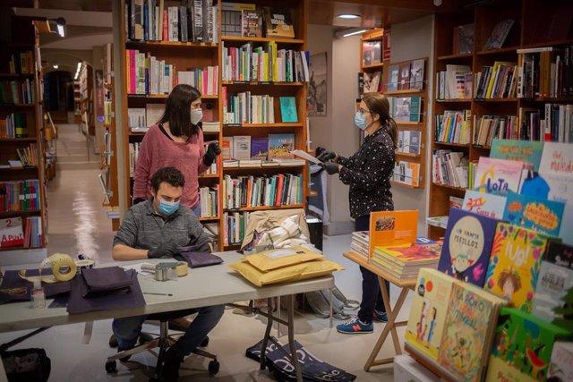 Trabajadores de la librería Laie Pau Claris librería-café ubicada en la calle catalana de Pau Claris, preparan libros y material antes de enviarlos. En Barcelona, Cataluña, (España), a 22 de abril de 2020 (archivo)