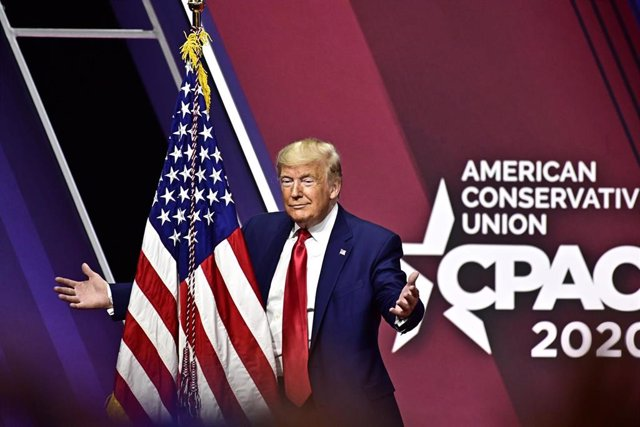 El presidente de Estados Unidos, Donald Trump, se dispone a abrazar una bandera del país norteamericano.