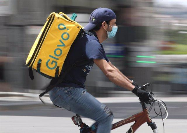 Un repartidor de Glovo munta una bicicleta durant la seva jornada laboral.